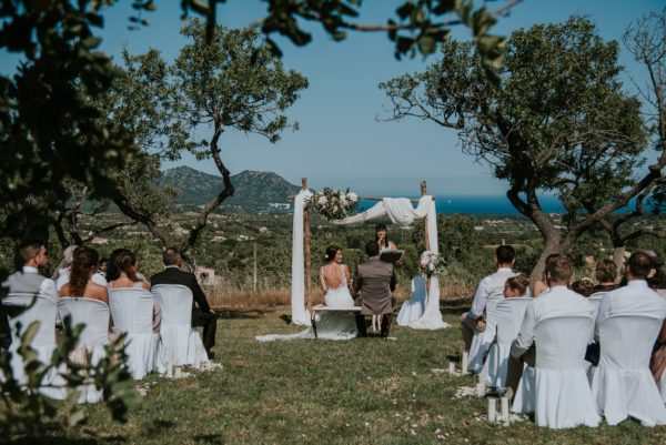 Weitblick auf die Hochzeitszeremonie. Grüne Bäume umrahmen das Bild.