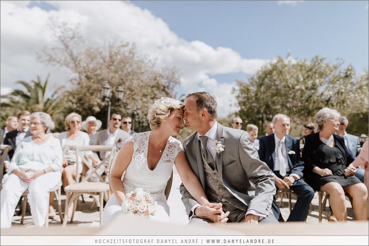 Das Brautpaar tief berührt sitzt Hand in Hand und Stirn an Stirn vor dem Altar.