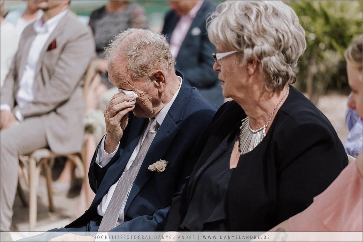 Der Brautvater trocknet sich eine Träne während der Zeremonie.