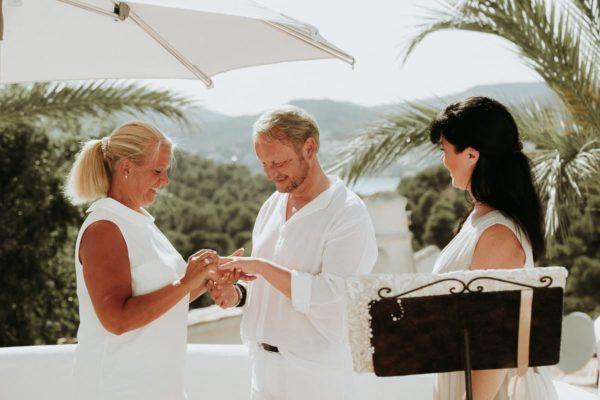 Ring anstecken während der Hochzeitszeremonie unter Palmen.
