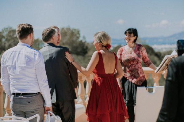 Vater, Braut und Bräutigam lachen herzlich als sie am Altar ankommen.