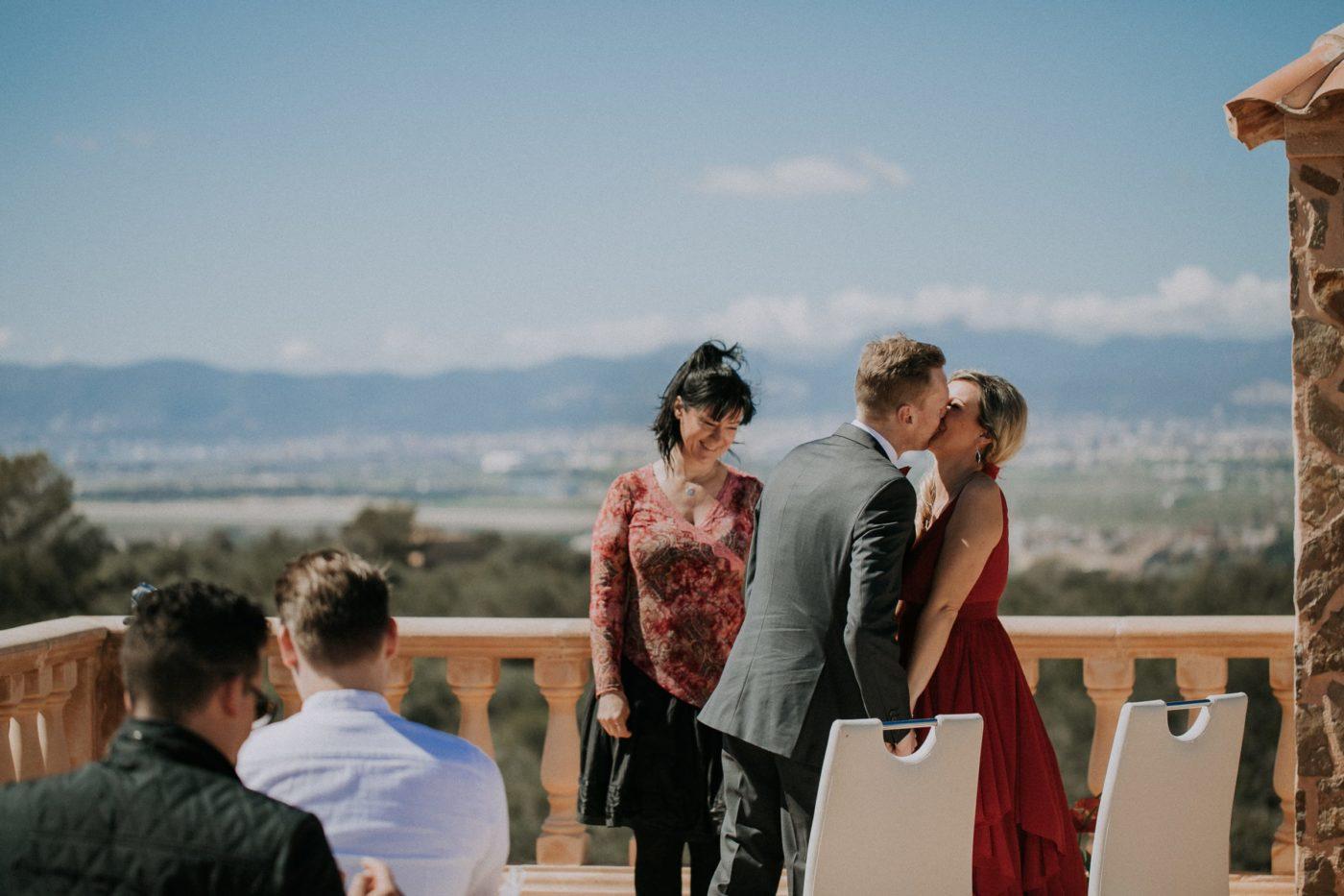 Das Brautpaar küsst sich verliebt. Ich lächle.