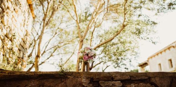 Ein hübscher Brautstrauss in einer alten Silberkanne auf einer mallorquinischen Mauer.
