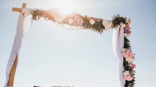 Der blumengeschmückte Hochzeitsaltar im sonnigen Gegenlicht.