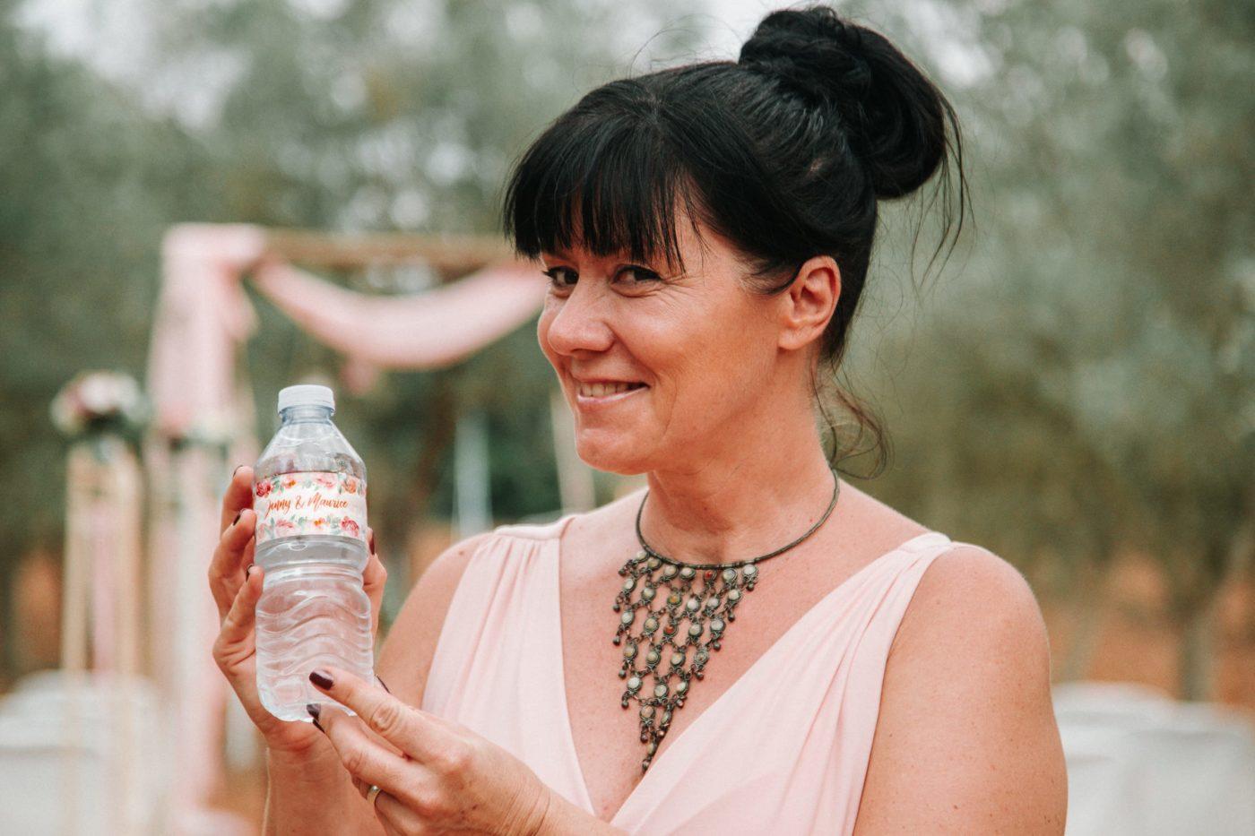 Ich zeige lächelnd eine Flasche Wasser in die Kamera die extra für unser Brautpaar mit deren Namen bedruckt wurde.