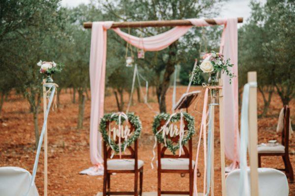 Die zauberhafte Hochzeitsdekoration in rosa inmitten eines Olivenhaines.