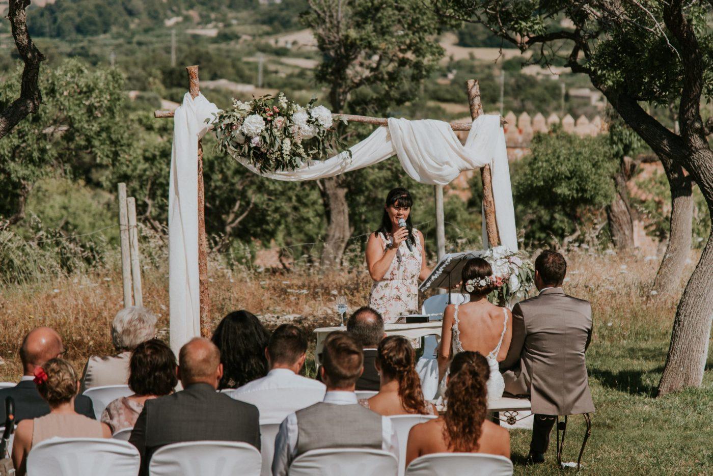 Die Hochzeitszeremonie von einem erhöhten Punkt fotografiert. Man sieht im Hintergrund das wunderschöne Grün der mallorquinischen Landschaft.