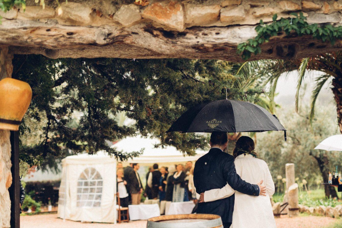 Das Brautpaar kommt im Regen mit einem Regenschirm zur Zeremonie.