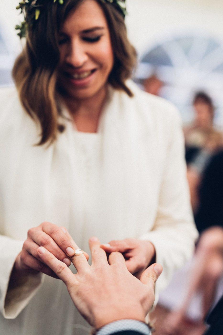 Die Braut steckt ihrem zukünftigen Mann den Ring an.