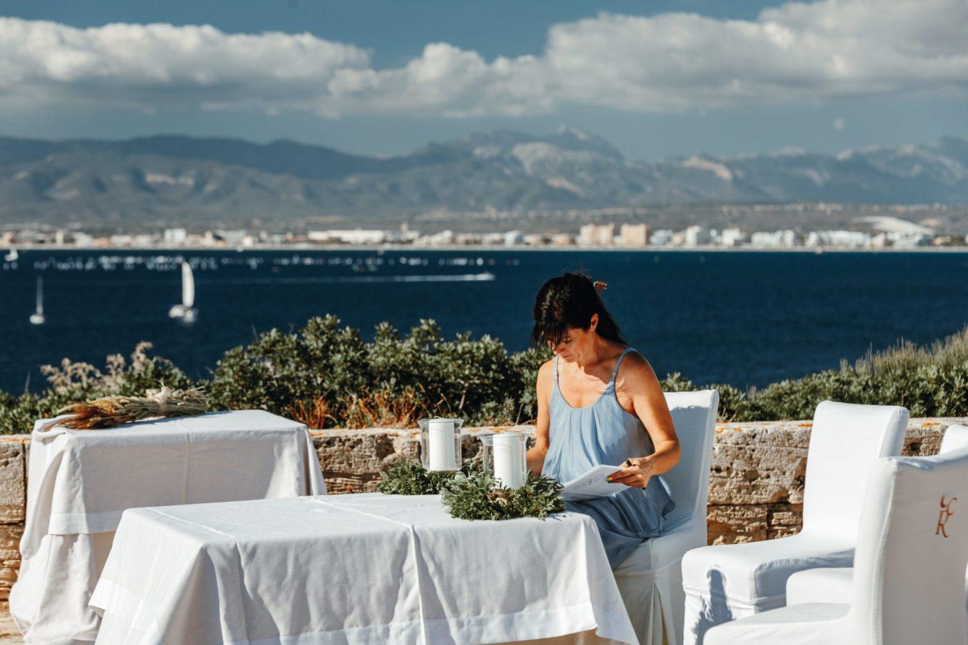 Ich sitze am Altar in der Sonne am Meer und bereite mich auf die bevorstehende freie Trauungszeremonie vor.