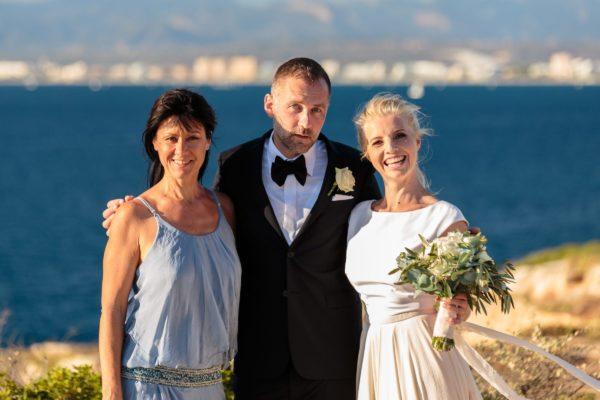 Ein hübsches Gruppenbild mit dem Brautpaar und dem Meer im Hintergrund.