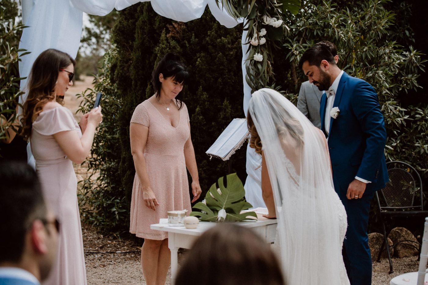 Das Brautpaar unterschreibt die symbolische Heiratsurkunde.
