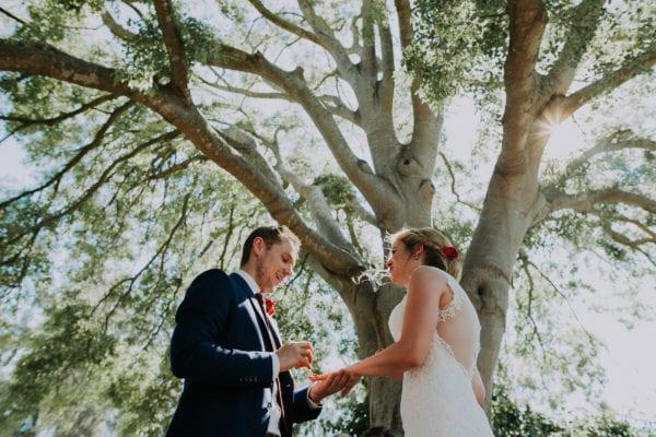 Der Bräutigam steckt seiner Braut verliebt den Ring an.